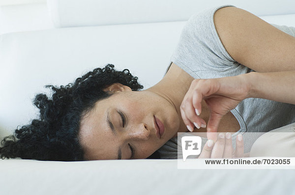 Young woman lying down  contemplating fingers