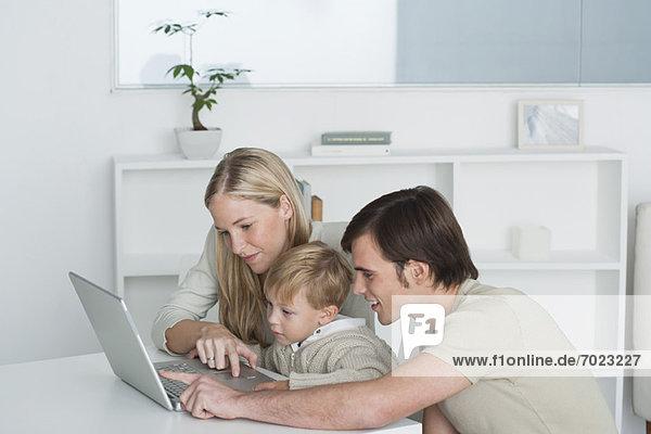 Eltern und kleiner Junge benutzen gemeinsam einen Laptop.