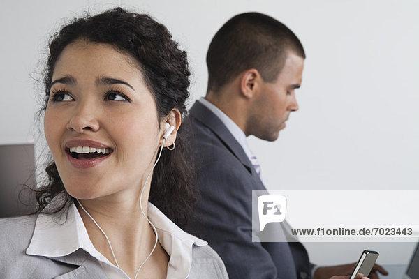 Frau hört Kopfhörer und träumt im Büro