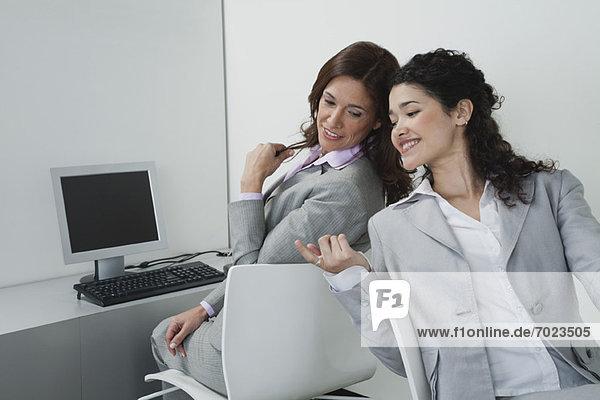 Weibliche Mitarbeiter chatten im Büro