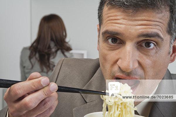 Der reife Geschäftsmann isst Ramen-Nudeln im Büro.