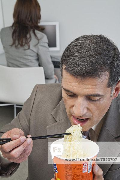 Geschäftsmann isst Ramen-Nudeln im Büro