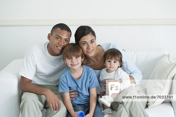 Familie sitzt zusammen auf dem Sofa  Porträt