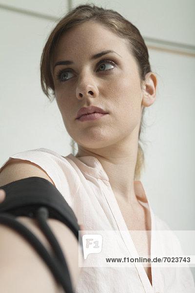 Junge Frau mit Blutdruckmessung  Blickwinkel niedrig