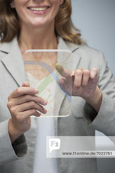 Frau mit Touchscreen-Technologie zur Darstellung der Karte auf transparentem Digital-Tablett