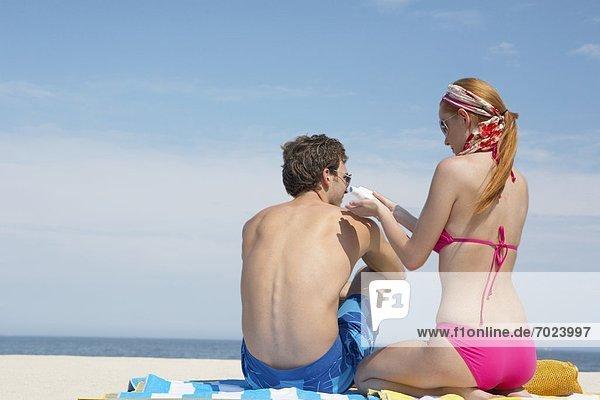 eincremen  verteilen  Frau  Mann  Strand  Sonnencreme  auftragen