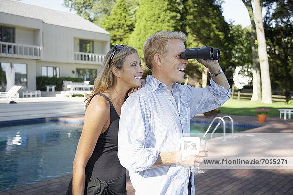 Couple using binoculars by pool