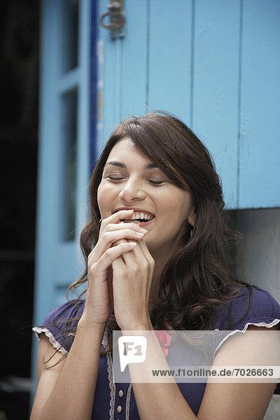 Junge Frau mit geschlossenen Augen lachen