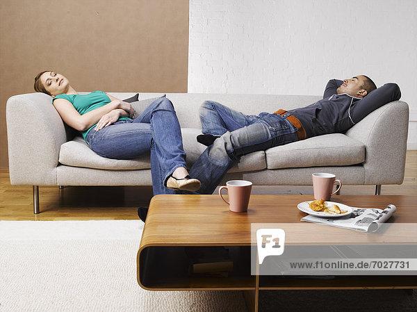 Junges paar entspannenden auf Sofa