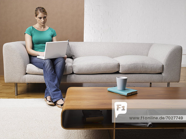 Young Woman Using Laptop on Sofa