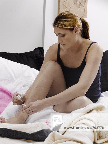 Junge Frau Malerei Fußnägel auf Bett