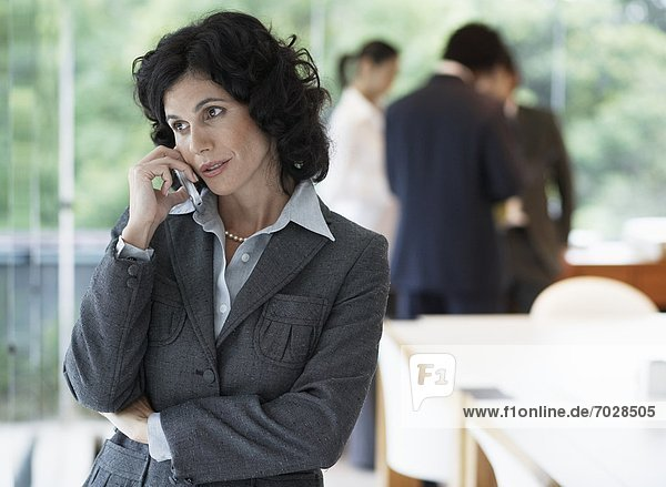 Businesswoman talking on phone  colleagues in background