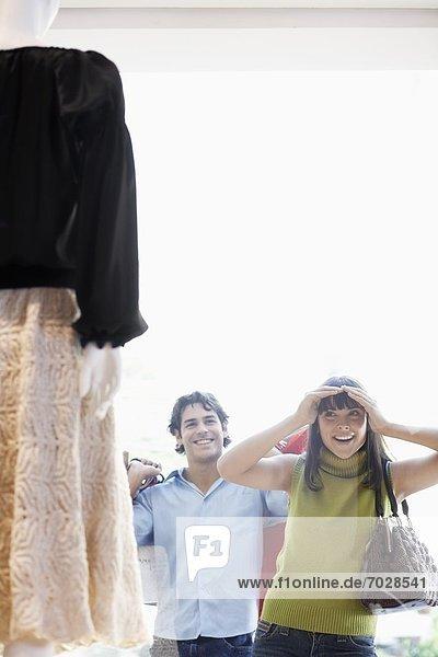 Woman window shopping  boyfriend in background