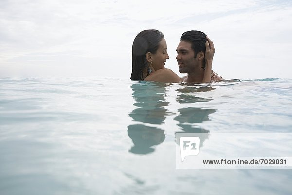 Young couple hugging in water (low angle view)  St. John  US Virgin Islands  USA
