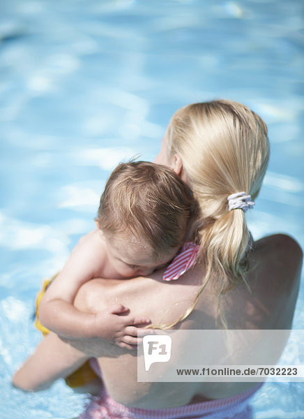 Mother Carrying Baby Boy in Swimming Pool