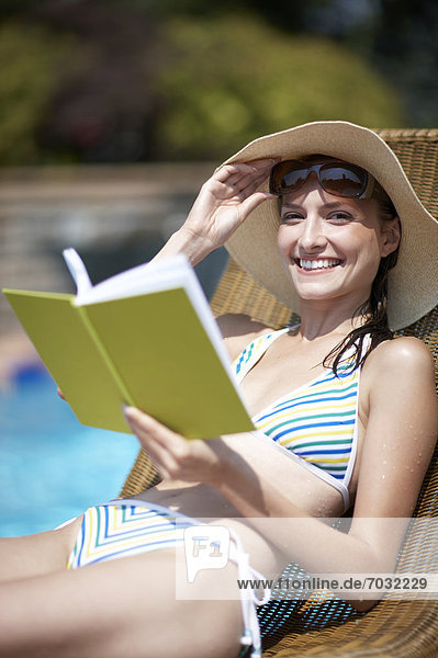 Happy Woman Reading Book by Pool