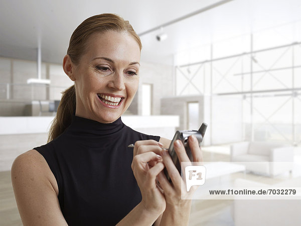 Happy Woman Using Electronic Organizer