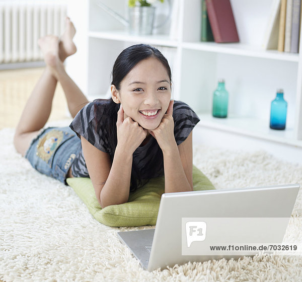 Mid Adult Woman Using Laptop on Floor