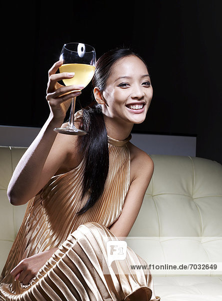 Mid-Adult Woman in Evening Dress Toasting With White Wine