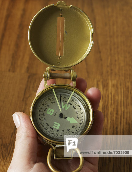 Person Holding Old-Fashioned Compass