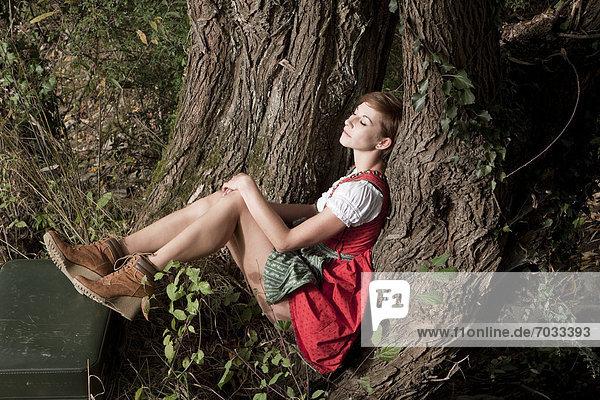 Frau im Dirndl sitzt an einem Baum Frau im Dirndl sitzt an einem Baum