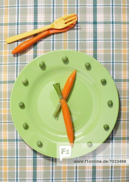 Grüner Teller mit Karotten und Erbsen in Form einer Uhr