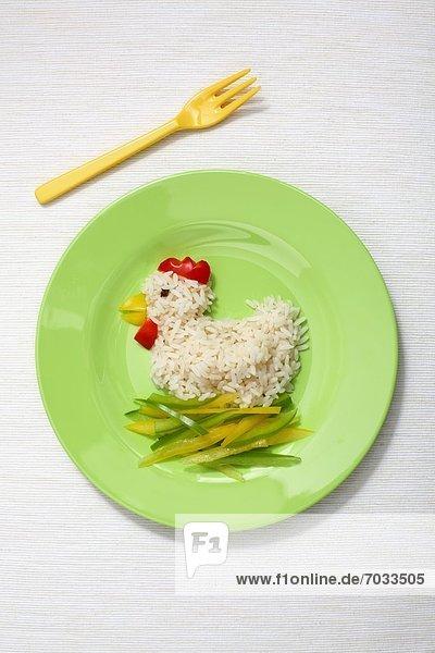 Kinderteller mit Reis und Paprika in Form eines Huhns Kinderteller mit Reis und Paprika in Form eines Huhns
