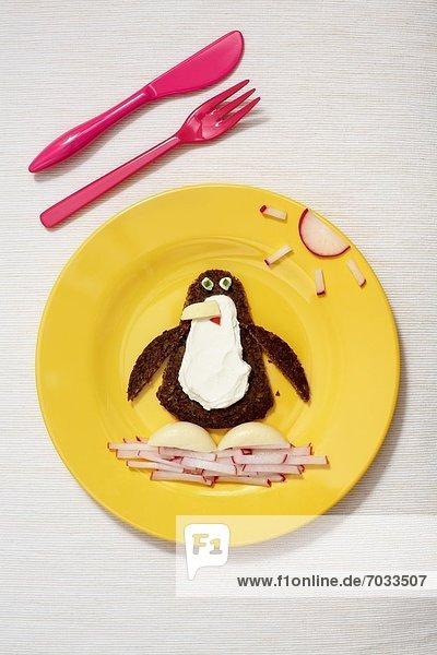 Kinderteller mit Vollkornbrot  Frischkäse und Radieschen in Form eines Pinguins Kinderteller mit Vollkornbrot, Frischkäse und Radieschen in Form eines Pinguins