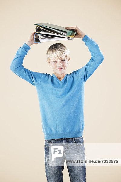 Blonder Junge mit Aktenordnern