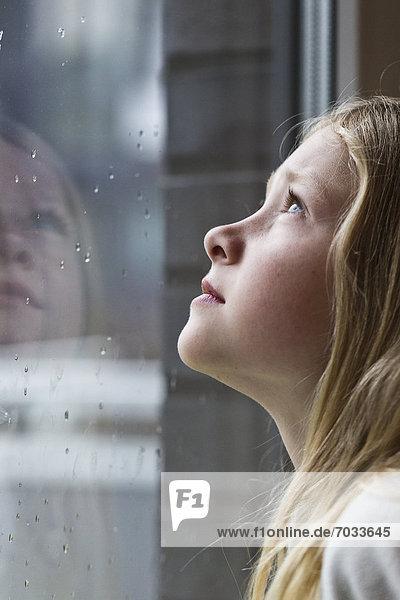 Blondes Mädchen schaut aus verregnetem Fenster