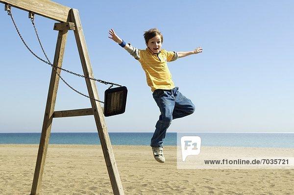 schaukeln schaukelnd schaukelt schwingen schwingt schwingend Strand Junge - Person springen Schaukel