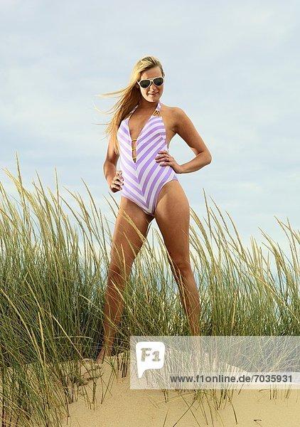 Woman In Swimsuit Posing On Beach