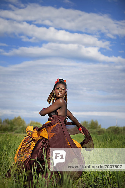 'A Young Woman In A Colourful Dress Twirling In A Field With Tall Grass