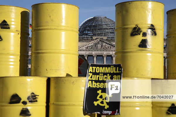 'Sign  lettering ''Atommuell zurueck an den Absender''  German for ''atomic waste - return to sender''  a stack of nuclear waste barrels in front of the Reichstag building  Berlin  Germany  Europe'