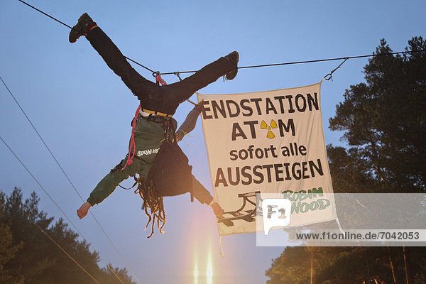 Protest against a nuclear waste transport  an activist of the environmental organization Robin Wood hanging above the transport route to the temporary storage facility for atomic waste  Gorleben  Lower Saxony  Germany  Europe