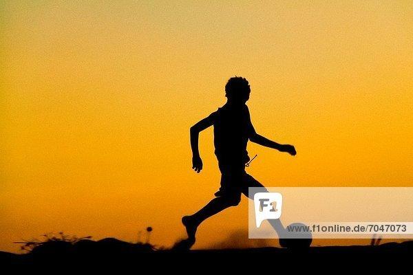 Strand  Junge - Person  Sonnenuntergang  klein  Gemeinschaft  angeln  Spiel  jung  Brasilien  Football