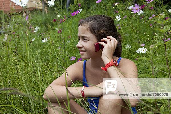 Mädchen  11 Jahre  telefoniert inmitten einer Blumenwiese in freier Natur