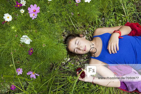Mädchen  11 Jahre  hört inmitten einer Blumenwiese in freier Natur Musik mit einem MP3-Player