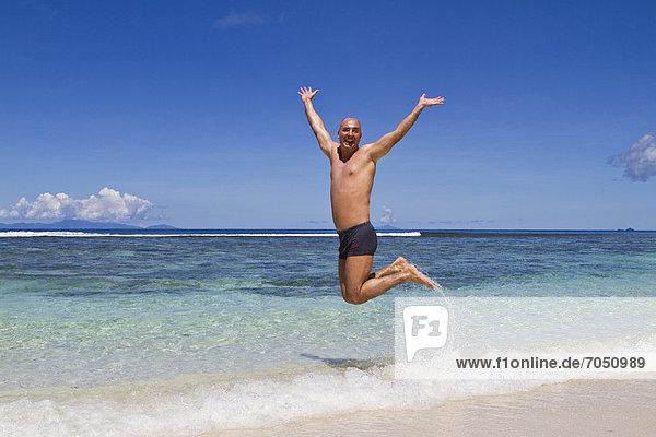 Mann  45 Jahre  macht vor Freude einen Luftsprung am Strand  Insel La Digue  Seychellen  Afrika  Indischer Ozean