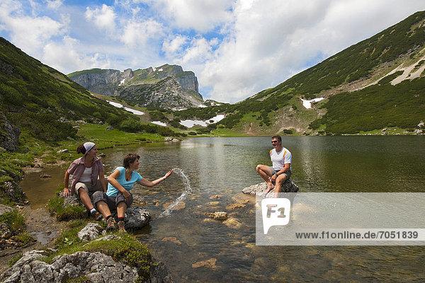 Hikers at a mountain lake  Lake Zireiner  Kramsach  Rofan Mountains  Tyrol  Austria  Europe