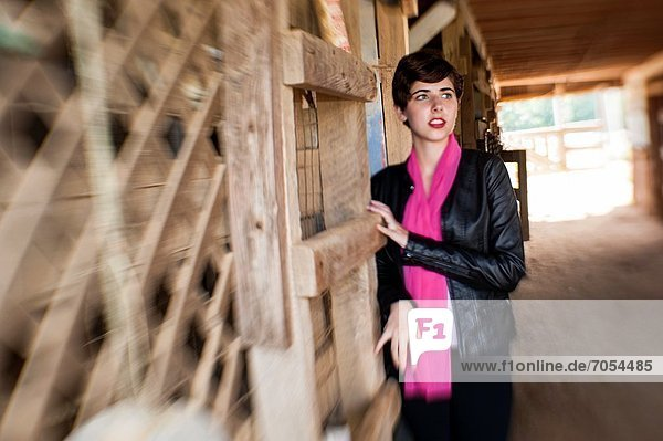 Portrait of young woman in a horse barn