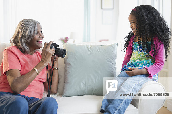 African American woman taking pictures of granddaughter