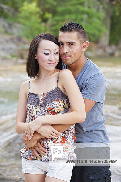USA  Texas  Leakey  Young couple embracing each other at river  smiling