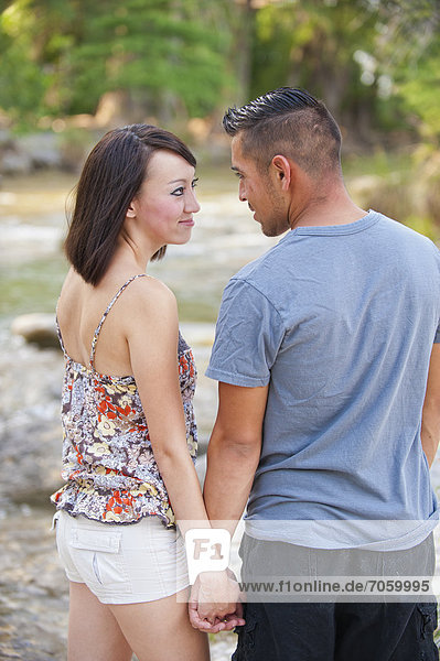 USA  Texas  Leakey  Young couple standing at riverside with holding hands  smiling