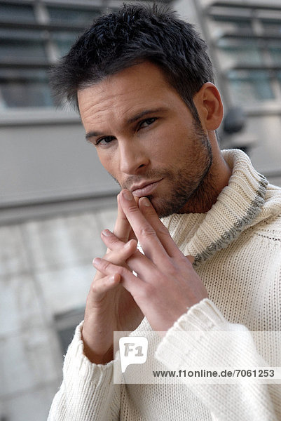 Man wearing a white turtleneck in a city.