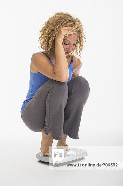 Waage - Messgerät  Studioaufnahme  hocken - Mensch  Frau  Gewicht  jung