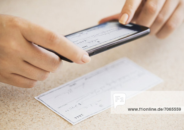 Close up of woman's hand doing online banking with mobile phone