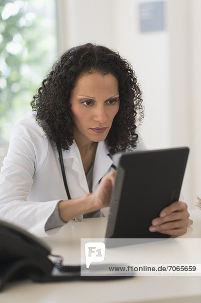 sitzend  benutzen  Portrait  Arzt  Büro  Tablet PC