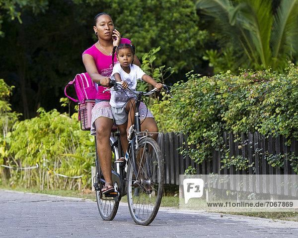 Frau mit Kind auf dem Fahrrad beim Telefonieren mit dem Handy  Insel La Digue  Seychellen  Afrika  Indischer Ozean