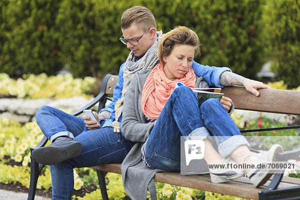 Paar auf Parkbank sitzend mit Lesemagazin und Mann mit Handy